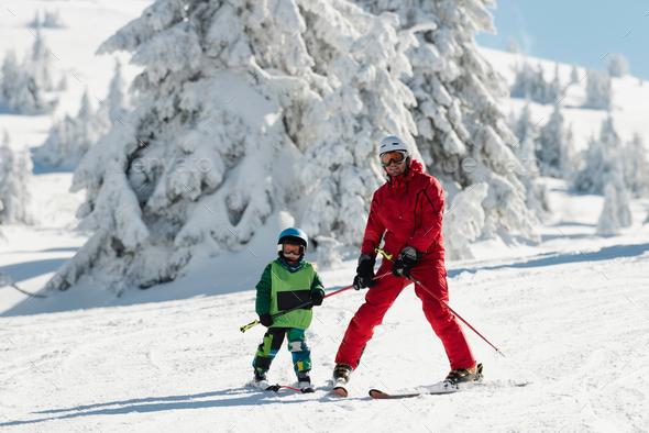 Ski instructor teaching little boy skiing - Stock Photo - Images