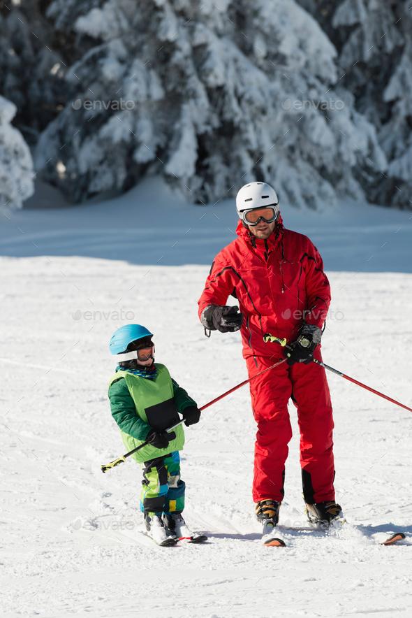 Ski instructor teaching little boy - Stock Photo - Images