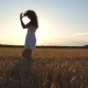 Beautiful Girl is Walking along Wheat Field - VideoHive Item for Sale
