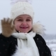 A Little Girl at the Age of 5 in the Winter, It's Snowing on the Street, She Looks at the Camera - VideoHive Item for Sale