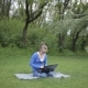 Young Girl Is Using Laptop Sitting On The Grass In The Park - VideoHive Item for Sale