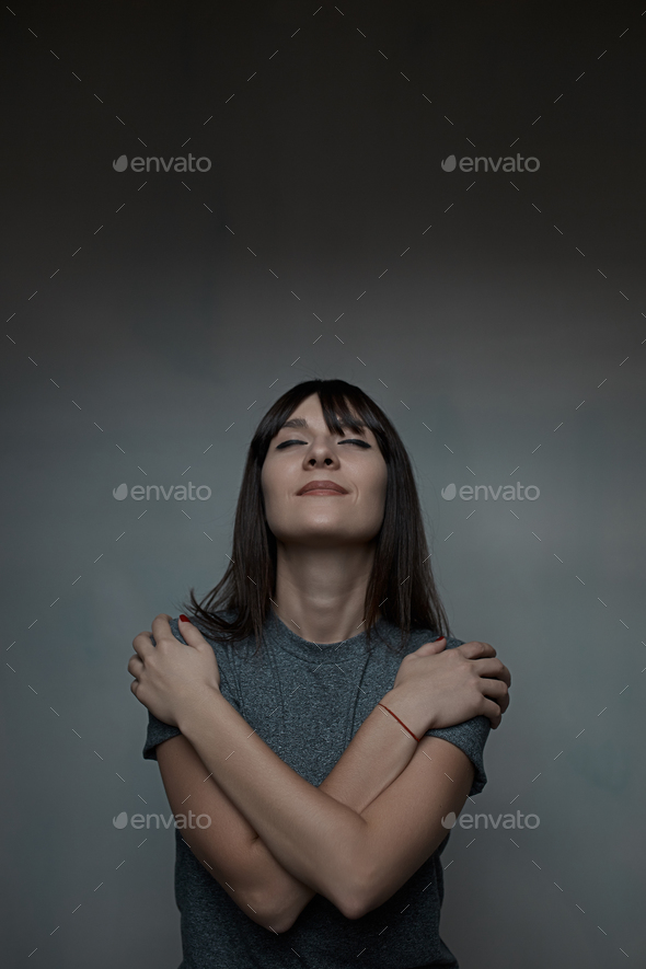 Close up portrait of woman embracing herself - Stock Photo - Images