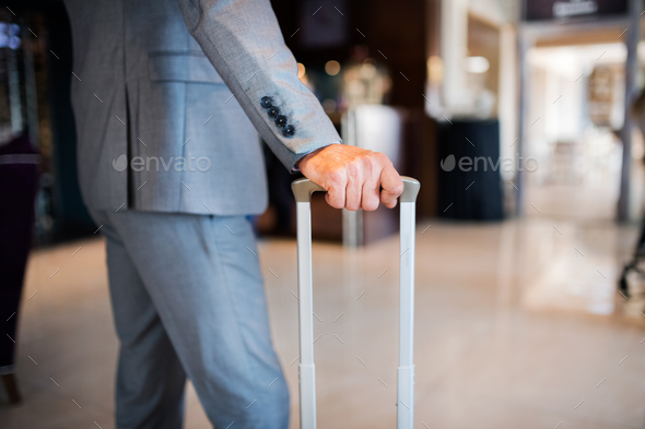 Businessman with suitcase in a hotel entrance hall. - Stock Photo - Images