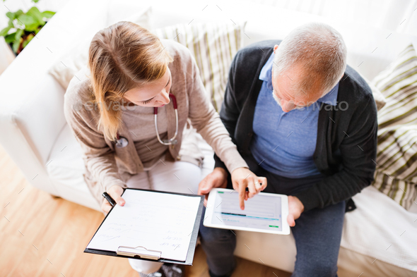 Health visitor and a senior man with tablet during home visit. - Stock Photo - Images