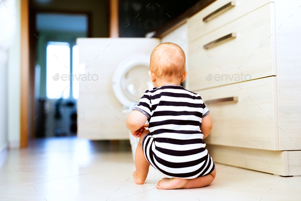 Baby boy by the washing mashine in the kitchen. - Stock Photo - Images