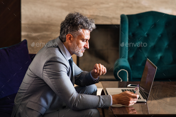 Mature businessman with laptop in a hotel lounge. - Stock Photo - Images