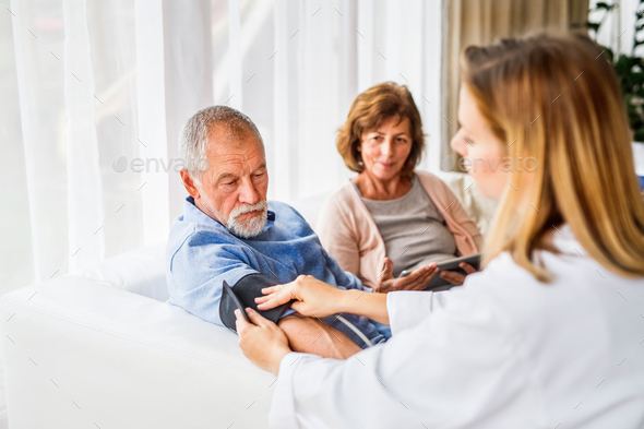 Female doctor checking blood pressure of senior man. - Stock Photo - Images