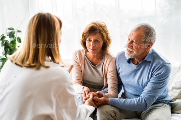 Female doctor talking to a senior couple. - Stock Photo - Images