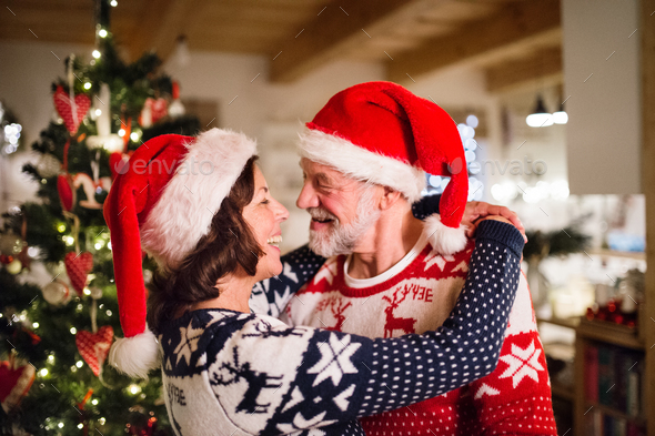 Senior couple with Santa hats at Christmas time. - Stock Photo - Images