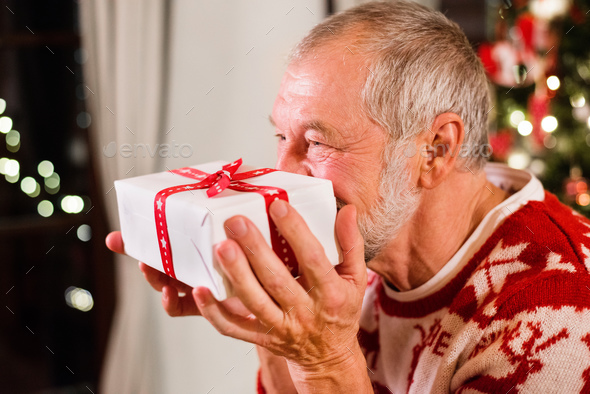 Senior man in front of Christmas tree holding a gift. - Stock Photo - Images