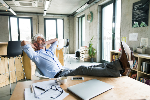Thoughtful mature businessman with smartphone in the office. - Stock Photo - Images