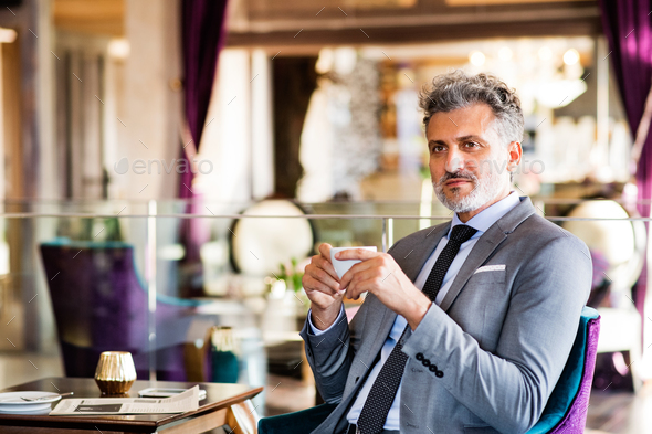 Mature businessman with coffee in a hotel lounge. - Stock Photo - Images