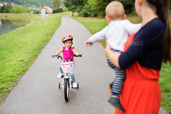 Little girl with her mother and brother in the nature. - Stock Photo - Images