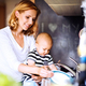 Young mother with a baby boy doing housework. - PhotoDune Item for Sale