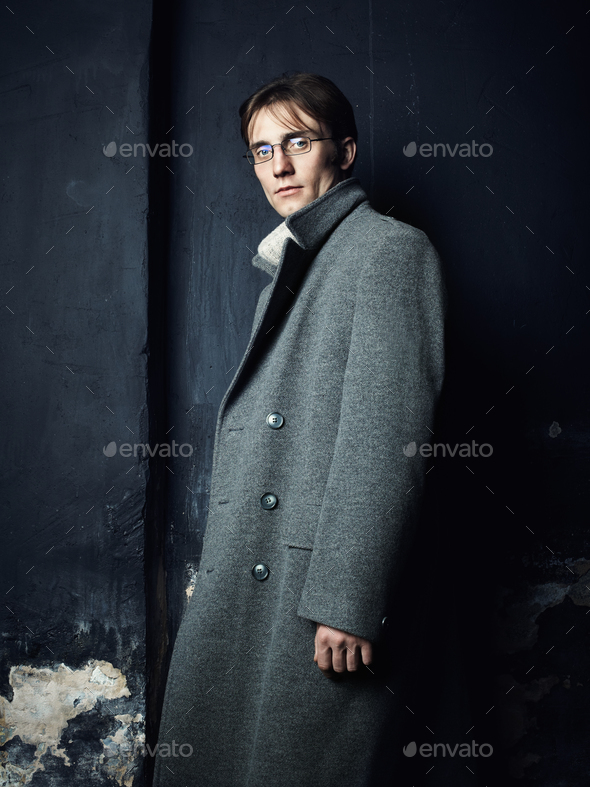 Artistic dark portrait of the young beautiful man in a gray coat - Stock Photo - Images