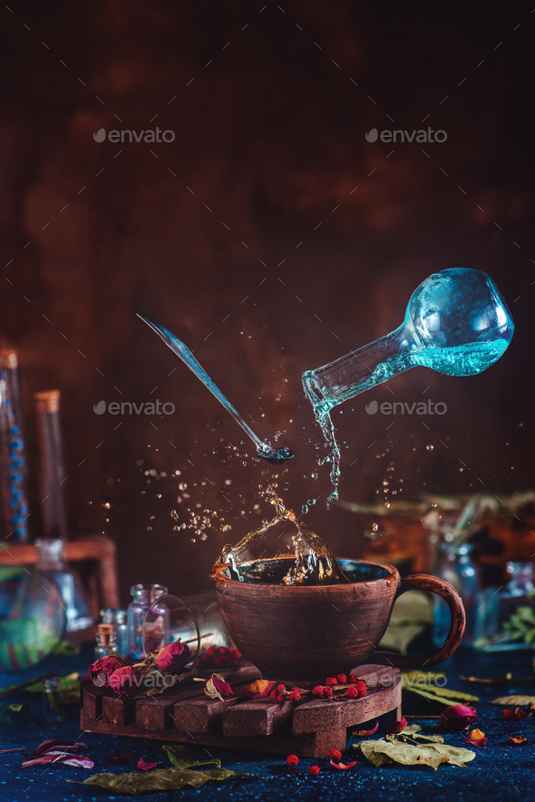 Flying potion bottle with pouring liquid in a magical still life. Brewing magical tea. - Stock Photo - Images