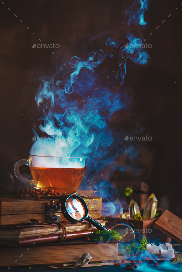 Hot cup of tea with a dense rising steam, magnifying glass, books and dried plants - Stock Photo - Images