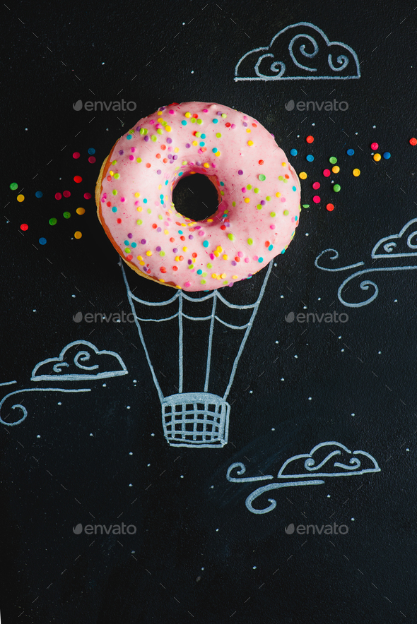 Pink glazed donut with chalk drawing of hot air balloon. Creative concept. Low key food photography. - Stock Photo - Images
