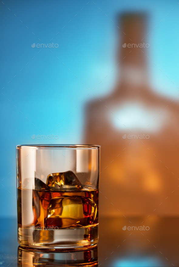 Glass of whiskey with ice against the background of the bottle - Stock Photo - Images