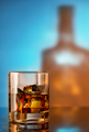 Glass of whiskey with ice against the background of the bottle - PhotoDune Item for Sale