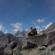 The Guy Sits on a Rock High in the Mountains - VideoHive Item for Sale