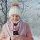 Young Woman Walks in Winter Park, Enjoys Smartphone - VideoHive Item for Sale