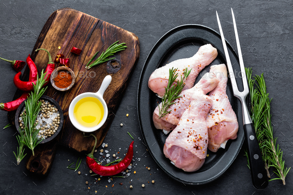 Chicken legs, drumsticks and ingredients for cooking, raw meat on black background, top view - Stock Photo - Images