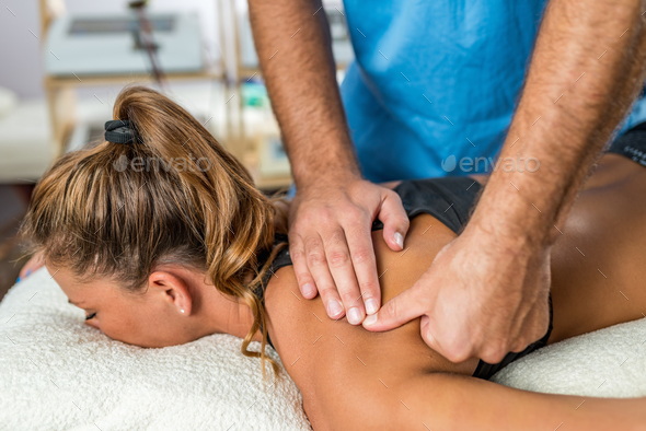 Osteopathy. Therapist applying strong pressure to shoulder muscl - Stock Photo - Images