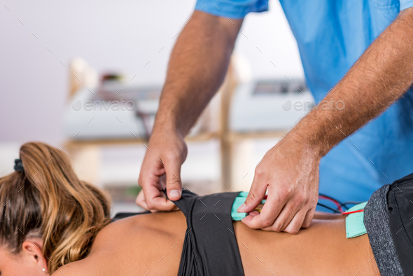 Electrical stimulation in physical therapy. Therapist positionin - Stock Photo - Images