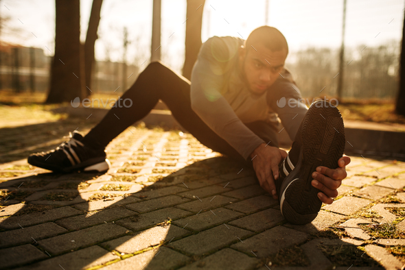 Male sportsman warming up before run - Stock Photo - Images