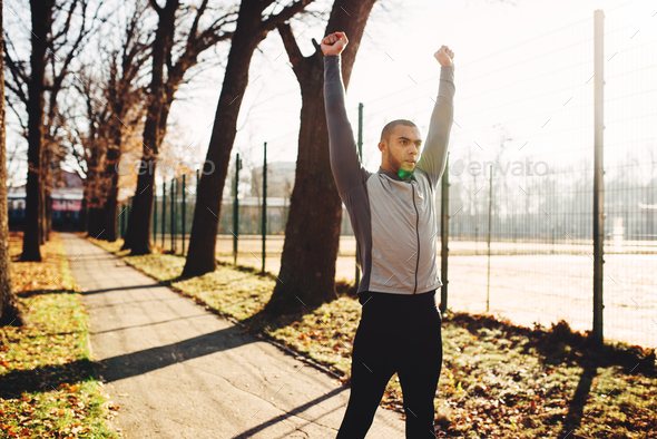 Sportsman warming up before run in autumn park - Stock Photo - Images