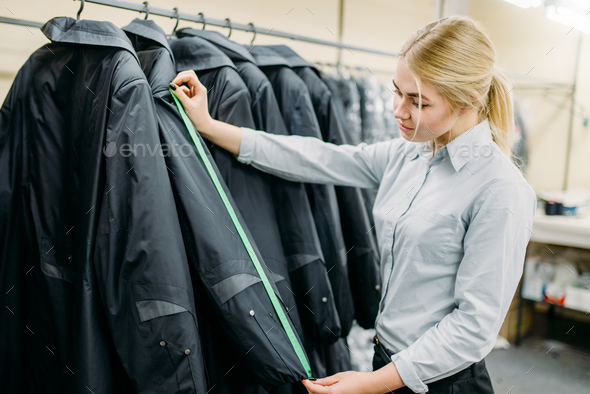 Clothes designer measures length sleeve jacket - Stock Photo - Images