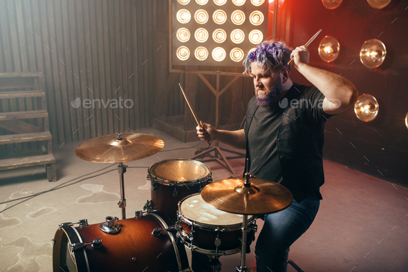 Bearded drummer with colorful hair, rock performer - Stock Photo - Images