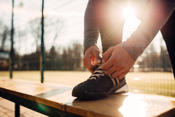 Male athlete doing stretching exercise before run - Stock Photo - Images