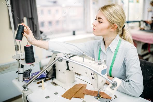 Female dressmaker sews on serger machine - Stock Photo - Images