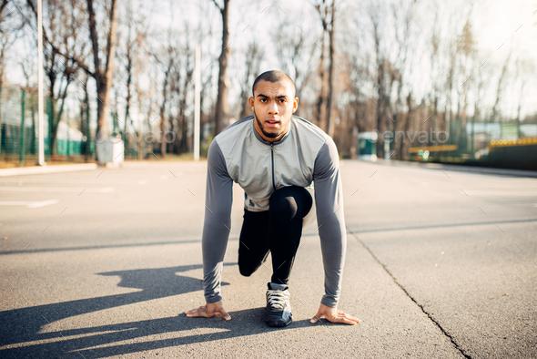 Male athlete prepares to run in autumn park - Stock Photo - Images
