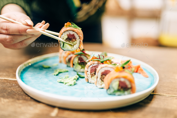 Male person eats sushi rolls with chopsticks - Stock Photo - Images