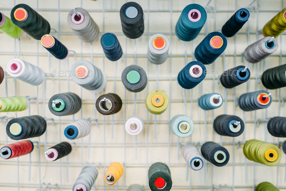Colorful threads on spools closeup, side view - Stock Photo - Images