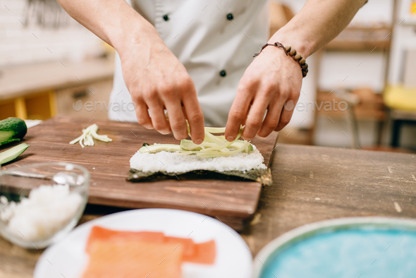 Male cook hands making sushi rolls, seafood - Stock Photo - Images
