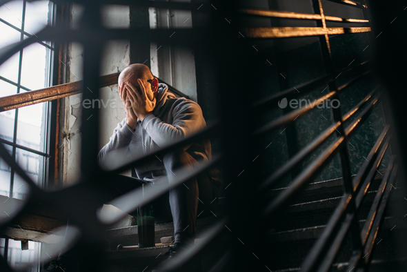 Male theif with bottle of alcohol sits on stairs - Stock Photo - Images