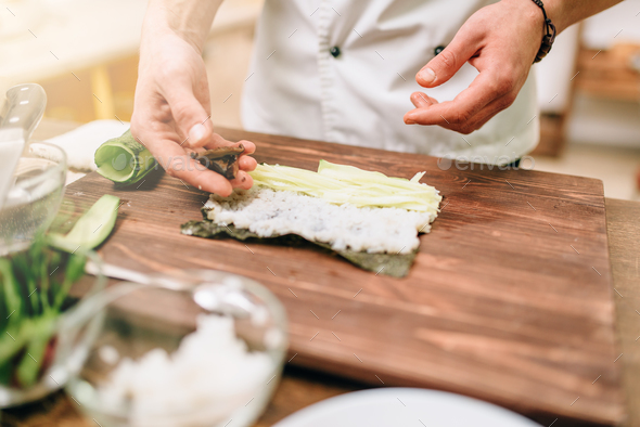 Male cook making sushi on wooden table, seafood - Stock Photo - Images