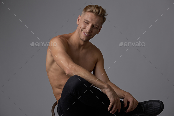 Attractive young man posing with naked torso sitting on a chair - Stock Photo - Images