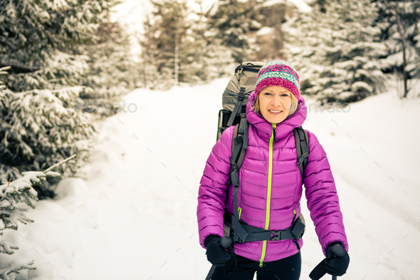 Happy woman walking in winter forest with backpack - Stock Photo - Images