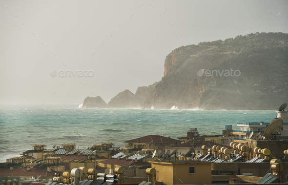 View over the stormy sea and castle hill of Alanya - Stock Photo - Images
