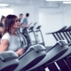 Adult Woman Runs on Treadmill at the Fitness Centre. Attractive Sporty Girl Running on the Treadmil - VideoHive Item for Sale