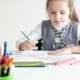Little Girl Drawing a Picture on White Room 7 Years Old Girl Drawing and Coloring on a Paper at - VideoHive Item for Sale