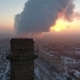 Aerial  Shot of a Big Industrial Tower with White Smoke at Sunset in Winter - VideoHive Item for Sale