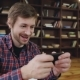 Excited Bearded Man Playing Games Om Smartphone with Pleasure in Home Interior - VideoHive Item for Sale
