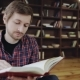 Young Handsome Caucasian Man Reading Book in Home Interior - VideoHive Item for Sale