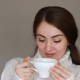 Young Beautiful Woman in a Warm Winter Sweater Drinks a Hot Drink From a White Cup and Looks at the - VideoHive Item for Sale